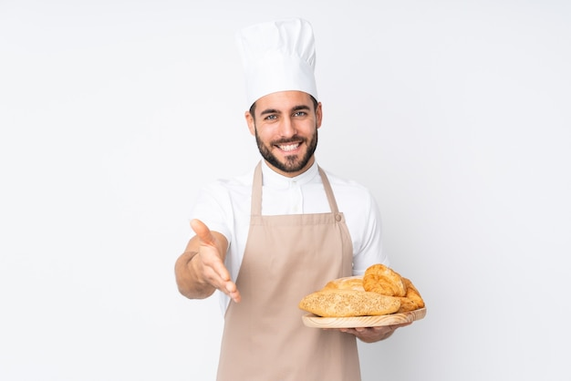 Padeiro segurando uma mesa com vários pães isolados na parede branca, apertando a mão após um bom negócio