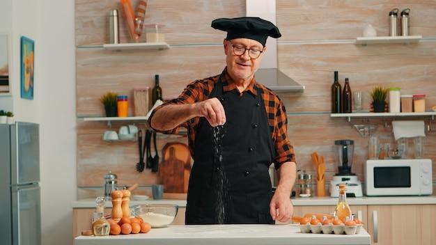 Padeiro sênior na cozinha em casa, colocando farinha de trigo sobre a mesa de madeira. chef idoso aposentado com bonete e avental polvilhando, peneirando ingredientes crus com a mão, assando pizza caseira, pão.
