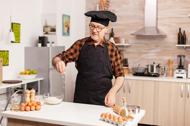 Padeiro sênior na cozinha em casa, colocando farinha de trigo sobre a mesa de madeira. chef sênior aposentado com bonete e avental, em uniforme de cozinha, polvilhando ingredientes peneirados com a mão.