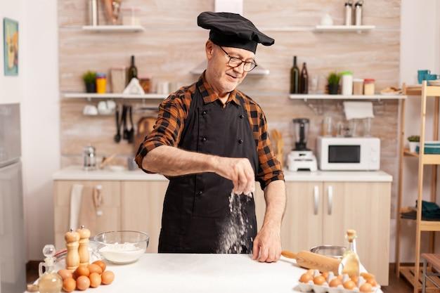 Padeiro sênior sorridente na cozinha de casa usando ingredientes biológicos para receita saborosa. chef aposentado com bonete e avental, em uniforme de cozinha, polvilhando ingredientes peneirados à mão.