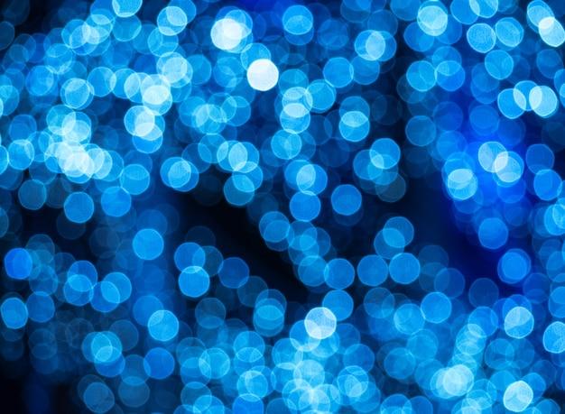 Padrão abstrato embaçado com pontos de luz azuis. fundo decorativo de lâmpadas de rua desfocadas Foto Premium