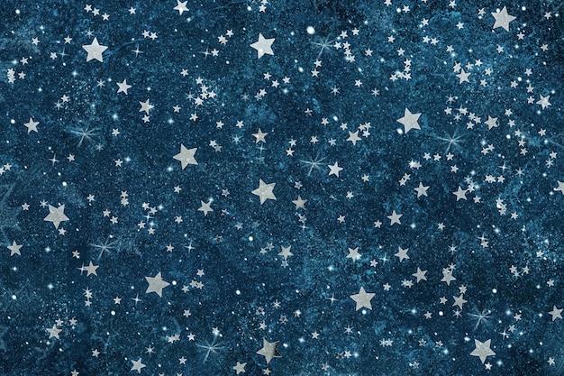 Padrão astronômico celestial com confete prateado em forma de estrela e glitter no fundo azul