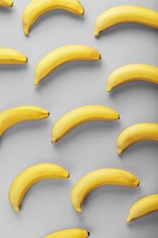 Padrão brilhante de bananas amarelas em um fundo cinza cores da moda de 2021