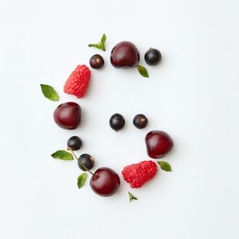 Padrão colorido de bagas da letra g do alfabeto inglês a partir de frutas maduras naturais - groselha preta