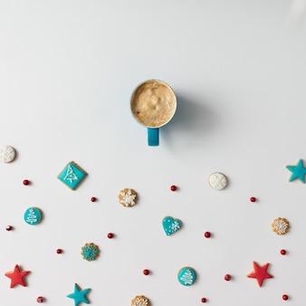 Padrão colorido feito de biscoitos de natal e frutas vermelhas com uma xícara de café
