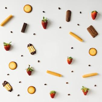Padrão colorido feito de grãos de café, morangos e biscoitos.