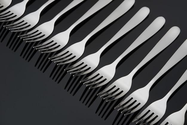 Padrão com muitos garfos de prata sobre fundo preto espelho. conceito,