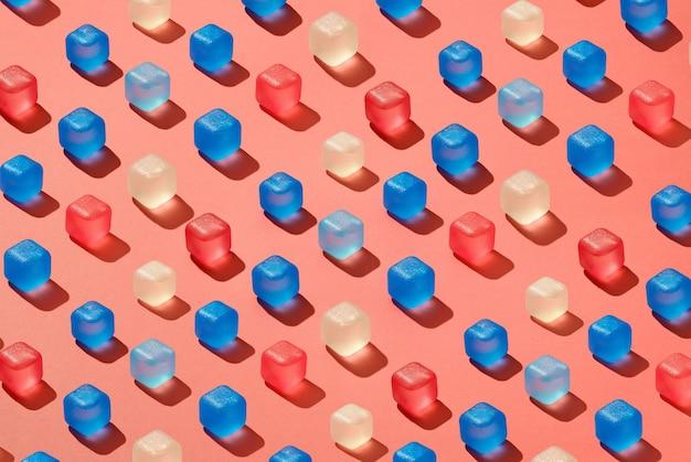Padrão criativo com cubos de gelo transparentes e coloridos com sombras duras