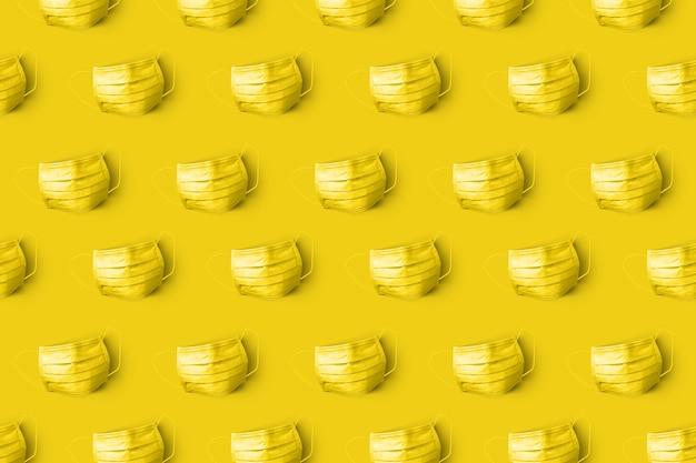 Padrão criativo de máscaras protetoras azuis médicas antibacterianas pintadas de amarelo na parede da mesma cor. flat lay conceito de prevenção de doenças respiratórias e vírus.