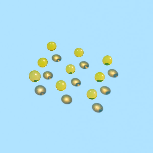 Padrão criativo de pequenas bolas de hidrogel flutuante com reflexos de sombras duras em uma parede de luz, copie o espaço.