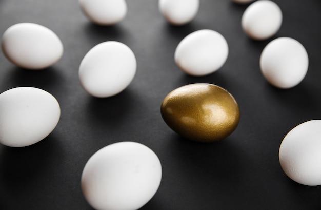 Padrão criativo feito de ovos de galinha brancos naturais e um ovo pintado de ouro sobre fundo preto