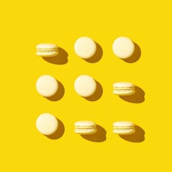 Padrão criativo regular de macarons de cookies amarelos brilhantes. cartão monocromático