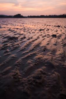 Padrão de areia na maré baixa na praia durante o pôr do sol