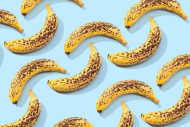 Padrão de banana manchado sobre fundo azul. comida de arte