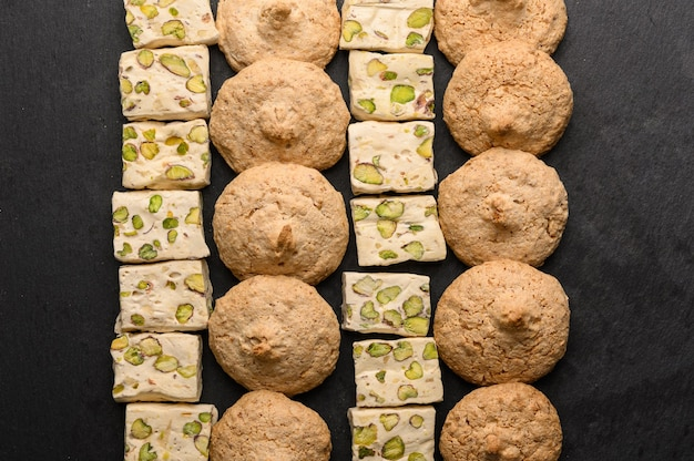 Padrão de biscoitos de amêndoa e nouvas em um fundo escuro.