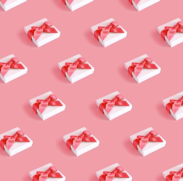 Padrão de caixas de presente brancas com um laço em um fundo rosa claro close-up