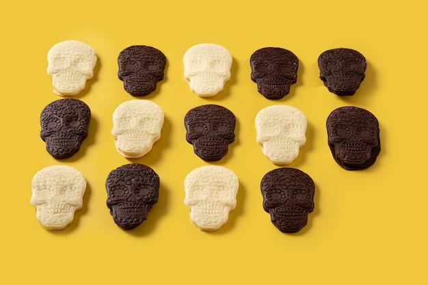 Padrão de caveiras de chocolate mexicano em fundo amarelo
