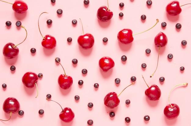 Padrão de cereja e mirtilo em fundo rosa