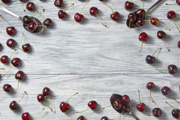 Padrão de cerejas recém-colhido de verão com lugar para texto em fundo cinza de madeira. conceito de alimentação orgânica limpa. postura plana