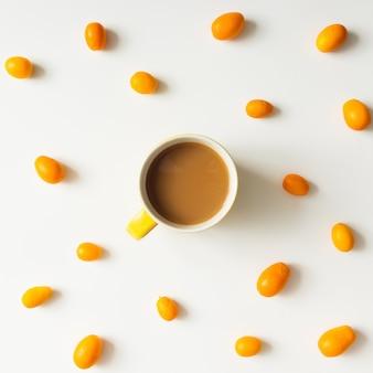 Padrão de colorido brilhante feito de frutas kumquat com xícara de café. postura plana.
