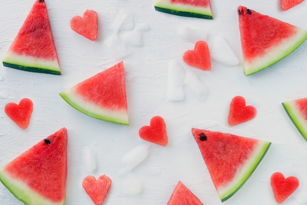 Padrão de corações e fatias de melancia. melancia fatiada em fundo branco com gelo. camada plana, vista superior. fatias de melancia no branco