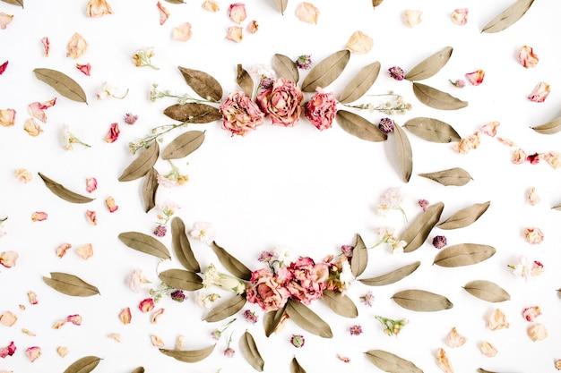 Padrão de coroa de armação redonda com rosas, botões de flores rosa, galhos e folhas secas na superfície branca