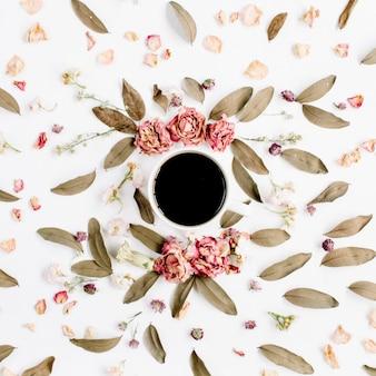 Padrão de coroa de armação redonda com rosas, xícara de café, botões de flores rosa, galhos e folhas secas na superfície branca