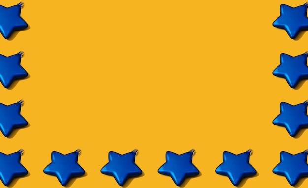 Padrão de decoração de bugigangas em forma de estrela azul de natal criativo em fundo de papel amarelo. conceito de leigo plano mínimo de ano novo com espaço de cópia.