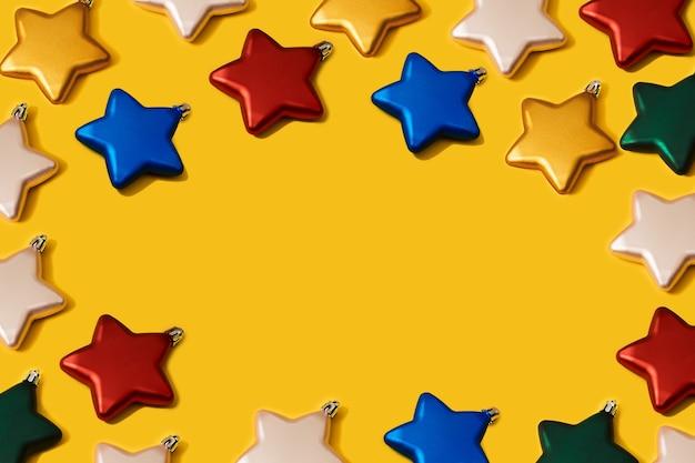Padrão de decoração de bugigangas em forma de estrela de cor vibrante de natal criativo em fundo de papel amarelo. conceito de leigo plano mínimo de ano novo com espaço de cópia.