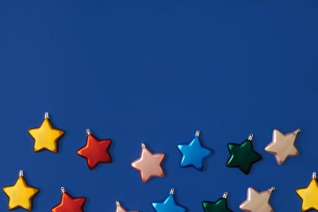 Padrão de decoração de bugigangas em forma de estrela de natal criativa em fundo de papel azul. conceito de leigo plano mínimo de ano novo.