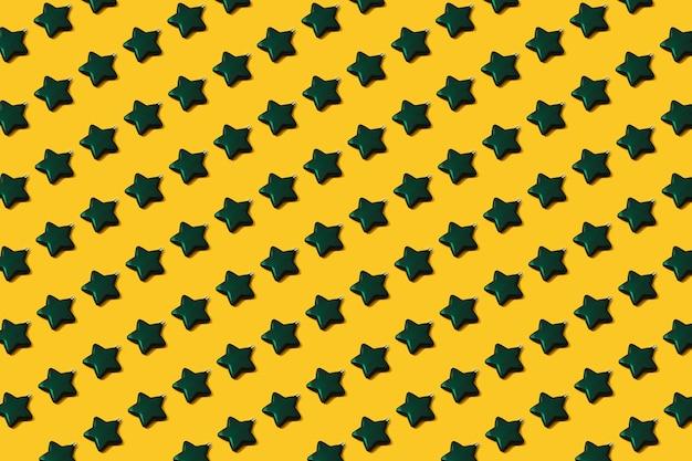 Padrão de decoração de bugigangas em forma de estrela verde de natal criativa em fundo de papel amarelo. conceito de leigo plano mínimo de ano novo.