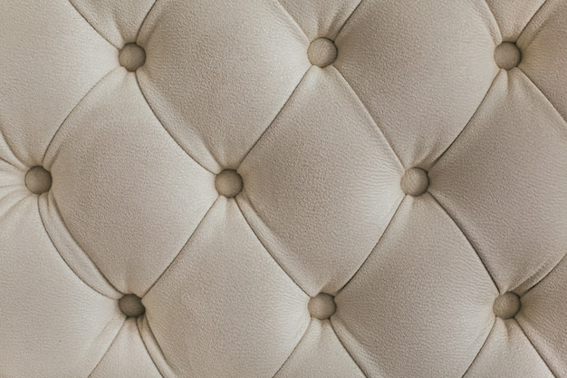Padrão de diamante em tecido de veludo bege claro com botões. conceito de plano de fundo. capa de sofá de móveis.