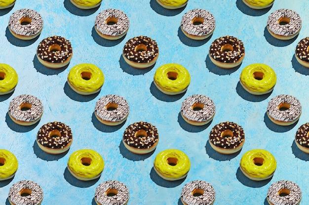 Padrão de donuts sem costura com esmalte branco, amarelo e marrom sobre um fundo azul.