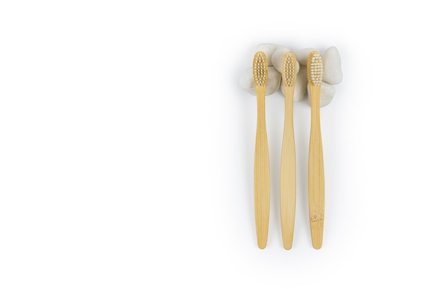 Padrão de escovas de dentes de bambu com pedras brancas em um fundo branco.