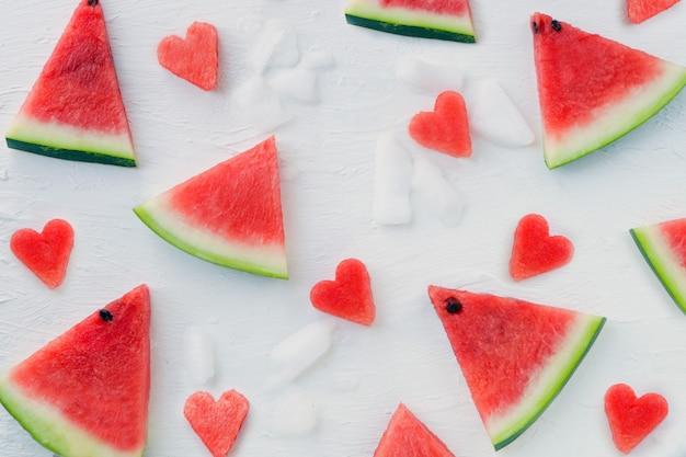 Padrão de fatias de corações e fatias de melancia melancia fatiada em fundo branco com gelo plano horizontal