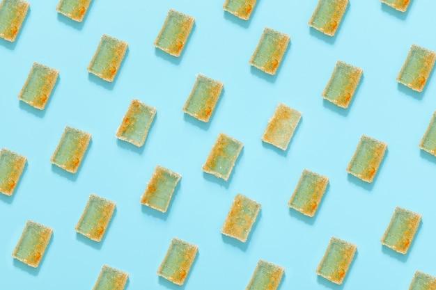 Padrão de fatias de geléia de laranja em açúcar sobre fundo azul. geléia de frutas cítricas. vista do topo