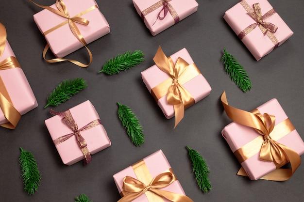 Padrão de férias de presentes variados, envolvidos em um pensamento rosa com um toldo de ouro e raminhos verdes
