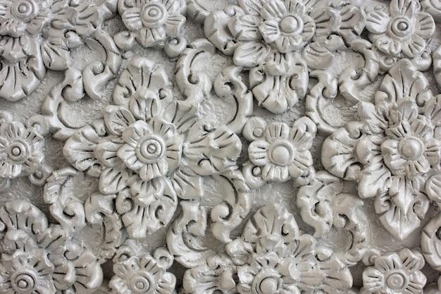 Padrão de flor cinza esculpida em design de estuque de parede nativa