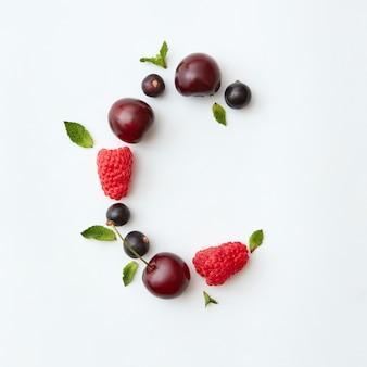 Padrão de frutas frescas colhidas do alfabeto inglês da letra c a partir de frutas maduras naturais - groselha preta