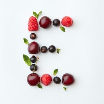 Padrão de frutas frescas do alfabeto inglês da letra e de frutas naturais maduras - groselha preta