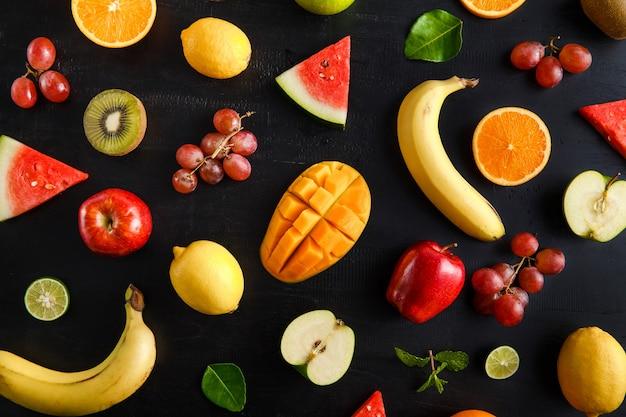 Padrão de frutas tropicais misturadas de vista superior em preto