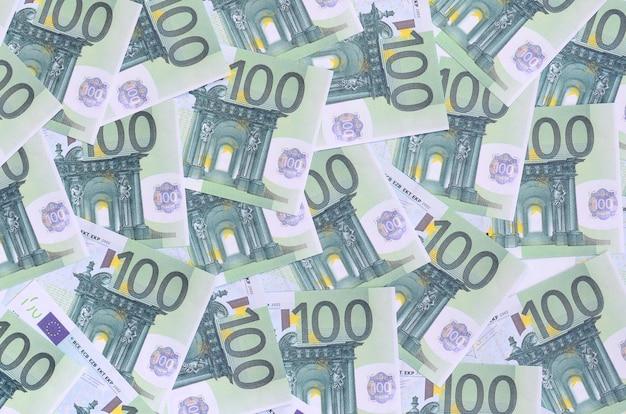 Padrão de fundo de um conjunto de denominações monetárias verdes de 100 euros. um monte de dinheiro forma uma pilha infinita