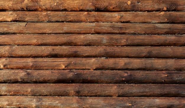 Padrão de fundo natural de uma parede de log. cabana de madeira ou celeiro sem pintura parede descascada com textura de fundo horizontal com espaço para cópia.
