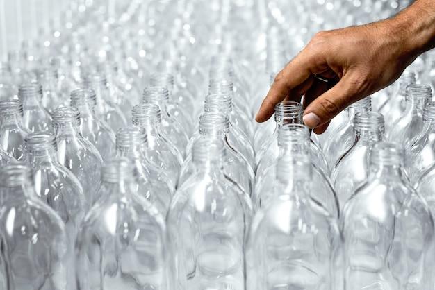 Padrão de garrafas de vidro transparente com uma mão no processo de fazer a bebida saudável