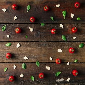 Padrão de ingredientes de pizza colorida feito de tomate cereja, manjericão e queijo na parede de madeira. conceito de cozinha.