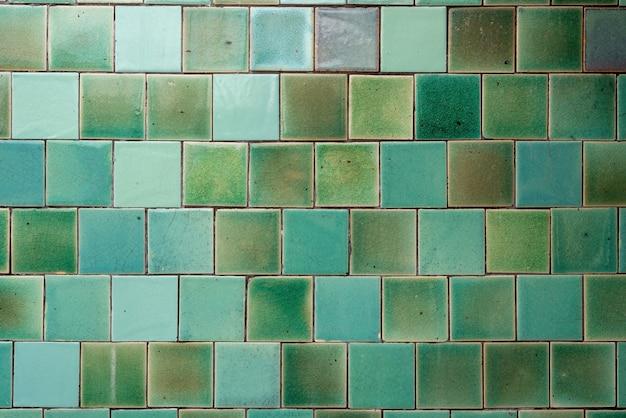 Padrão de ladrilhos quadrados dispostos em uma grade em tons de azul esverdeado