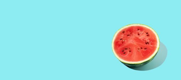 Padrão de melancia fatiada sobre fundo azul. fruta de verão, baga. cor negrito. sombras modernas e mínimas. conceito do dia da melancia - 3 de agosto. copie o espaço.
