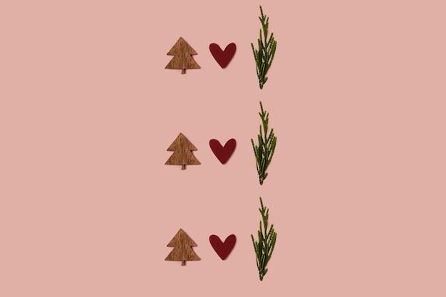 Padrão de natal feito com enfeite de coração vermelho de árvore de natal de madeira e galho verde