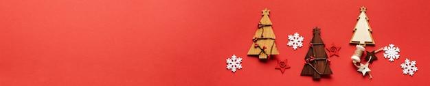 Padrão de natal feito de brinquedos de árvore de natal de madeira, flocos de neve e estrelas no vermelho. postura plana. bandeira. brincar.