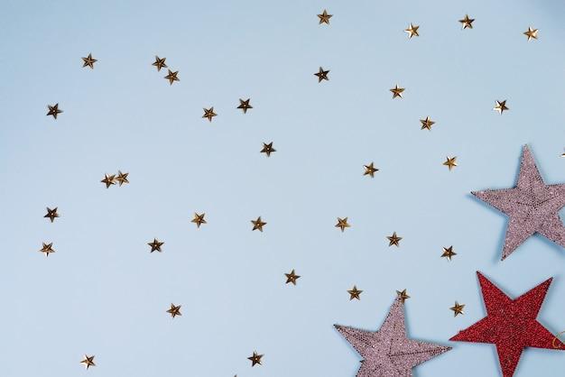 Padrão de natal feito de estrelas douradas, prateadas e vermelhas no azul